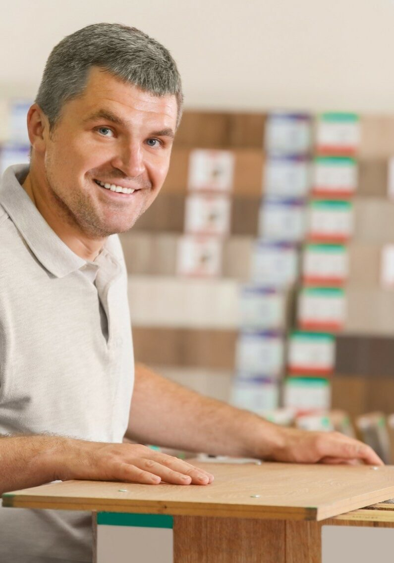 Man choosing laminate samples in Mesa, AZ hardware store | Noble Floors LLC